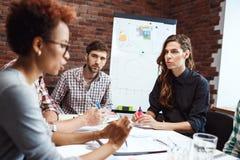 Collega's die nieuwe ideeën bespreken op commerciële vergadering royalty-vrije stock afbeeldingen