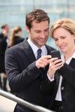 Collega's die telefoon bekijken Stock Foto