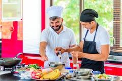 Collega's op het werk: Thaise en Europese chef-koks bij keuken het doen royalty-vrije stock foto