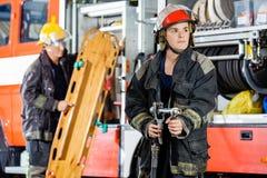 Collega sicuro di Holding Hose While del pompiere fotografia stock libera da diritti