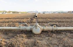 Collegamenti di tubi del metallo di irrigazione sul campo recentemente seminato Fotografia Stock Libera da Diritti
