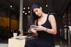 Collegamento abbastanza femminile alla radio sul telefono mentre riposando nella caffetteria accogliente nell'aria fresca Fotografie Stock