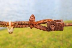 Collegamento del primo piano del cavo metallico d'acciaio arrugginito dell'imbracatura con la b confusa immagini stock libere da diritti