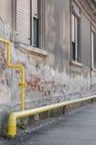 Collegamento di tubo giallo e una casa con le finestre con le imposte Fotografia Stock