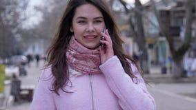 Collegamento mobile, colloqui femminili moderni sullo smartphone e sguardo da parte all'aperto