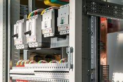 Collegando i cavi con il cavo trascina agli interruttori nel pannello di controllo elettrico fotografia stock libera da diritti