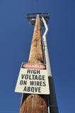 Collegare ad alta tensione del pericolo sopra il segno sul palo Fotografie Stock