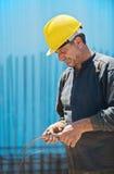 Collegare di taglio dell'operaio di costruzione con le pinze Fotografia Stock