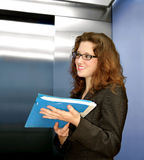 After College. Young woman standing in an elevator with mail in her hands Stock Photo