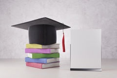 College ad concept. Abstract graduation hat and colorful book pile placed on concrete background with empty banner. College ad concept. Mock up, 3D Rendering Royalty Free Stock Photo