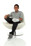 College age man relaxing in a modern chair Stock Photos