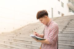 College asian male student holding book in campus.  Royalty Free Stock Photos