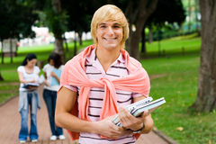 College boy. Young handsome college boy in campus, background is his classmates Royalty Free Stock Image