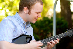 College Boy Concentrating on Guitar. A typical american college boy concentrating on playing a guitar. Short hair, shallow depth of field, selective focus Royalty Free Stock Images