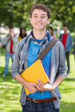 College boy holding books with blurred students in park Royalty Free Stock Photos