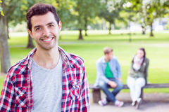 College boy smiling with blurred students sitting in park Royalty Free Stock Photo