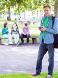 College boy text messaging with blurred students in park Stock Photography