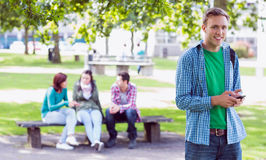 College boy text messaging with blurred students in park Royalty Free Stock Photography