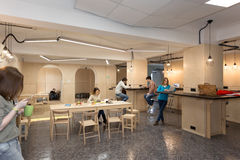 College Campus Kitchenette Area and Young People around. Wooden Table and Walls in College Campus Kitchenette Area and young People staying sitting around Royalty Free Stock Photo