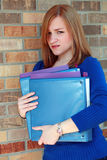 College Caution. Portrait of pretty college age girl with books making a face Royalty Free Stock Photography