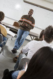 College Class. Male lecturer in front of students in class Stock Image