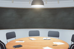 College classroom with round wooden table and blackboard Stock Photos