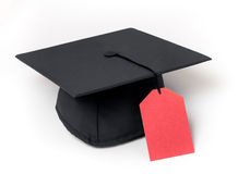 College costs. Mortarboard with a price tag as a tassle on a white background Royalty Free Stock Photos