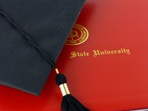 College Diploma and Cap. Black graduation cap with tassle on top of red diploma Stock Photo