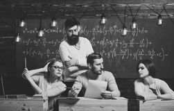 College education concept. Students, group mates speaking, asking for advice or cheating while teacher watching them. Bearded teacher, lecturer, professor stock image