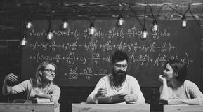 College and education concept. Students, young scientists fall in love with professor chalkboard background. Girls. Happy students looking with adoration at stock photo