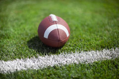 College football at goal with defocused background. College football sits at the goal line on a defocused grass field stock photography
