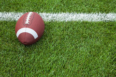 College football at the goal line. A college football sits at the goal line on a grass field royalty free stock photos