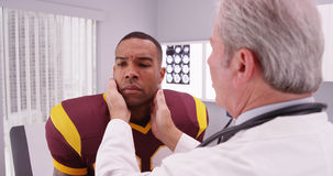 College football player having senior doctor review his concussi Stock Image