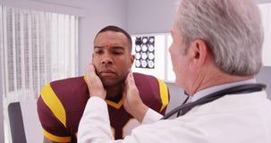 College - Football-Spieler, der älteren Doktorbericht sein concussi hat Stockbild
