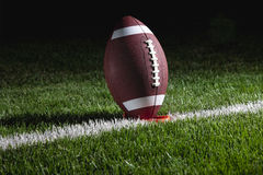 College football on tee at night ready for kick of. A college football on a tee at night sits on a yard marker ready for kick off Royalty Free Stock Photo