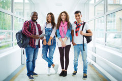 College friends in corridor. Friendly students in casual-wear standing in college corridor Royalty Free Stock Image