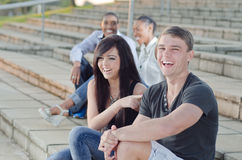 College Friends laughing. College Friends sitting together smiling and having a happy conversation Royalty Free Stock Image