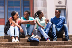 College friends sitting. Group of cute african american college friends sitting on stairs royalty free stock photo