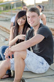 College Friends 3. College friends smiling and being cheerful  with other friends in background Stock Image
