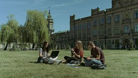 College friends using electronic devices on campus lawn. Cheerful college students studying with electronic devices and discussing university project while stock footage