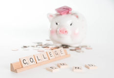 College Fund Concept. Scrabble letters spell out College Fund with out of focus piggy bank with graduation cap and coins in background.  on white background Stock Photo