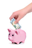 College Funds. Child putting money in a piggy bank Stock Images
