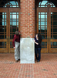 College Games. Young couple play hide and seek around the brick pillar at the entrance to the college dormatory Royalty Free Stock Photos