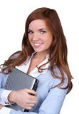College girl carrying a laptop. With a cute smile over white background stock photo