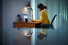 College Girl Female Student Studying At Night. Young woman with laptop computer for homework. Tired hispanic girl and college education. Female student studying Royalty Free Stock Photos