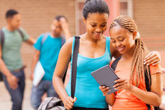 College girl friends tablet. Beautiful african college girl friends using tablet computer Royalty Free Stock Image