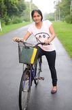 College girl on her cycle, at the middle of road. Stock Images