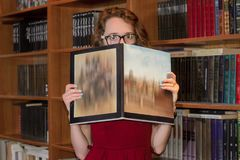 College girl hiding behind book. Portrait of a curly girl hiding behind book looking at the camera Royalty Free Stock Images