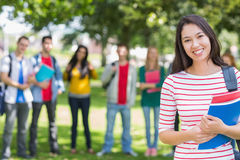 College girl holding books with blurred students in park. Portrait of college girl holding books with blurred students standing in the park Royalty Free Stock Image