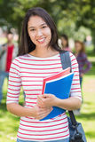 College girl holding books with blurred students in park Stock Photo